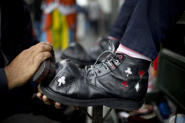 A clown has his shoes shined during a march commemorating the Peruvian clown day in Lima Peru, Monday, May 25, 2015. (Photo by Rodrigo Abd/AP Photo)