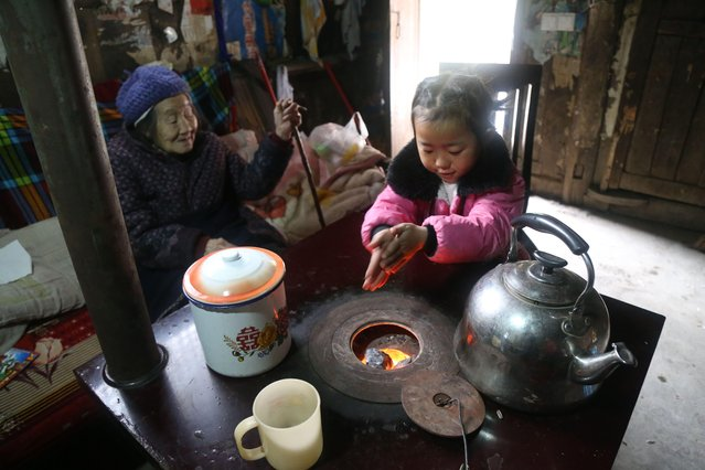 5-year-old Chinese girl Wang Anna burns coal to warm herself and her her great-grandmother at home in Zhuyuan village, Guizhou province, China on March 3, 2017. (Photo by Imaginechina/Rex Features/Shutterstock)
