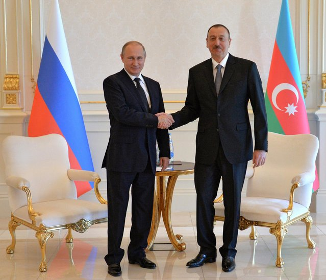 Russian President Vladimir Putin, left, and Azerbaijani President Ilham Aliyev shake hands during their meeting at the Zagulba residence outside Baku, Azerbaijan, Saturday, June 13, 2015. Russian President Vladimir Putin attended the opening ceremony of the the 2015 European Games in Baku on Friday.  (Alexei Druzhinin/RIA-Novosti, Kremlin Pool Photo via AP)