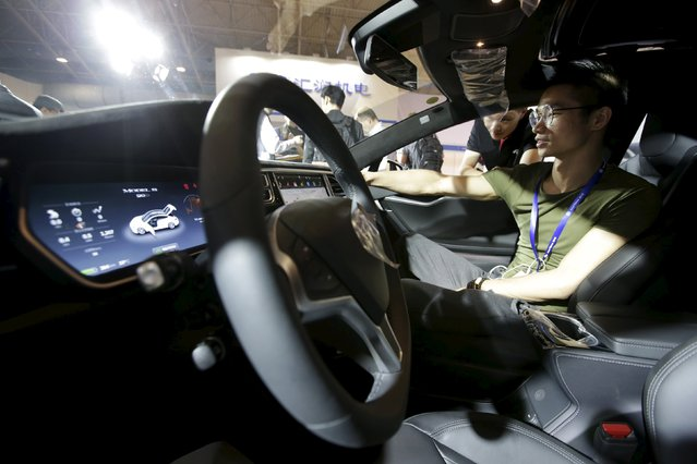 A visitor checks a Tesla Model S car during the Auto China 2016 in Beijing, China, April 25, 2016. (Photo by Jason Lee/Reuters)
