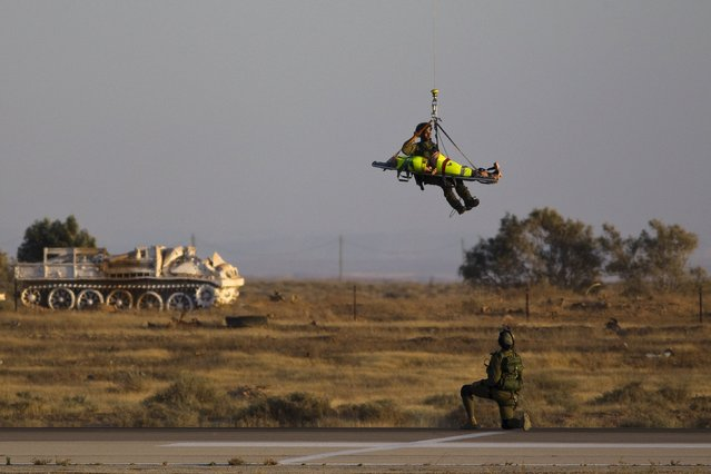 An Israeli Air Force Black Hawk (not seen) helicopter demonstrates the evacuation of a wounded person during the graduation ceremony of air force pilots at Hatzerim air base in southern Israel June 25, 2015. (Photo by Amir Cohen/Reuters)