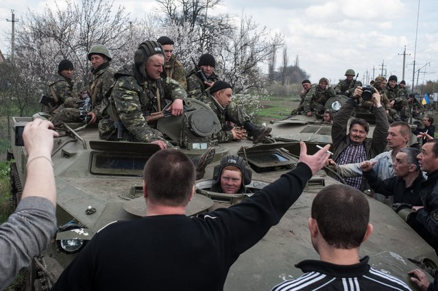 People block a column of Ukrainian Army combat vehicles on their way to the town of Kramatorsk on Wednesday, April 16, 2014. The central government has so far been unable to rein in the insurgents, who it says are being stirred up by paid operatives from Russia and have seized numerous government facilities in at least nine eastern cities to press their demands for broader autonomy and closer ties with Russia. (Photo by Evgeniy Maloletka/AP Photo)