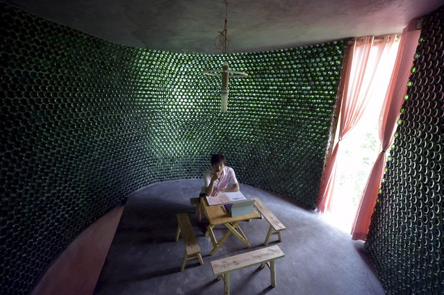 College graduate Li Rongjun sits in a building made of 8,500 beer bottles, near his home in Lanya village of Chongqing municipality, China, June 26, 2015. Li, who graduated from college with an engineering degree this year, spent more than four months and over 70,000 yuan ($11,270) to complete the 29-square-metre building with the help of his father. (Photo by Reuters/Stringer)