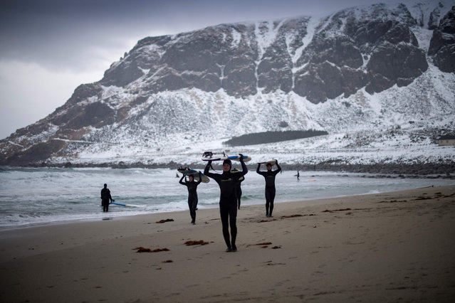 Novice surfers leave the beach at Unstad along the northern Atlantic Ocean on March 12, 2017, where the water temperatures is at five degrees centigrade and the air temperature is at minus two degrees centigrade. (Photo by Olivier Morin/AFP Photo)