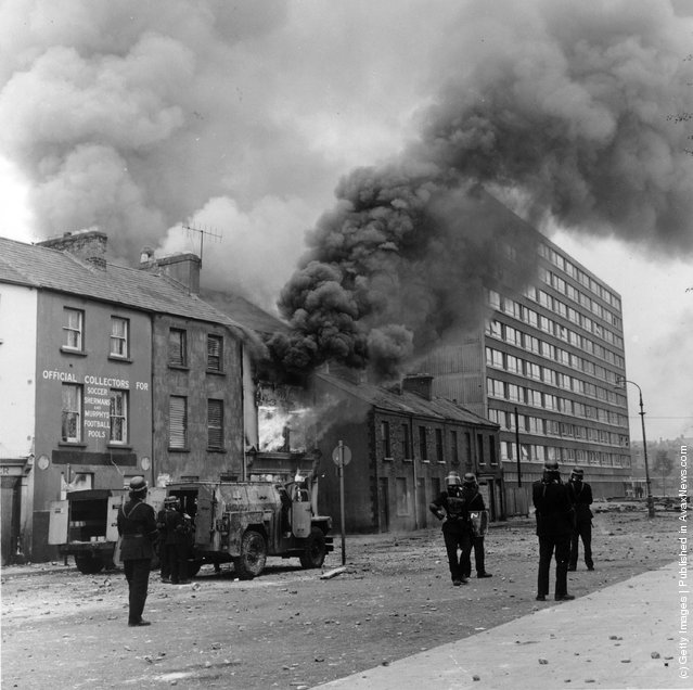 1969:  Heavy black smoke billows from a building after a bomb attack in the Bogside area of Belfast. Firemen are in attendance