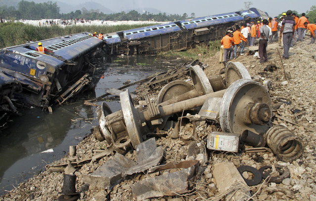 Rescue workers and onlookers stand next to derailed coaches of a passenger train in the northeastern Indian state of Assam April 16, 2014. Dozens of passengers on Wednesday were injured after the engine and ten coaches of the train derailed in Assam, local media reported. (Photo by Reuters)
