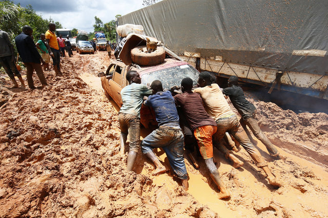 Men push a car stucking in the mud on a motorway in Nimba County, Liberia, 28 July 2019. Most highway roads in the rural parts of the country are unpaved. The government of President George Weah has promised to build roads to connect all big cites of Liberia. (Photo by Ahmed Jallanzo/EPA/EFE)