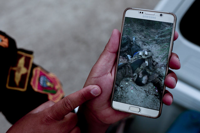 In this March 20, 2016 photo, Maj. Mohammed Hussein, an officer with Iraq's elite counterterrorism forces, shows a photo of a slain Islamic State group militant still wearing in a suicide vest, taken during fighting that freed the city of Ramadi from IS control earlier this year. As they fled, the militants destroyed some buildings and booby-trapped others with explosives, leaving behind an empty prize for government forces retaking the city. (Photo by Maya Alleruzzo/AP Photo)