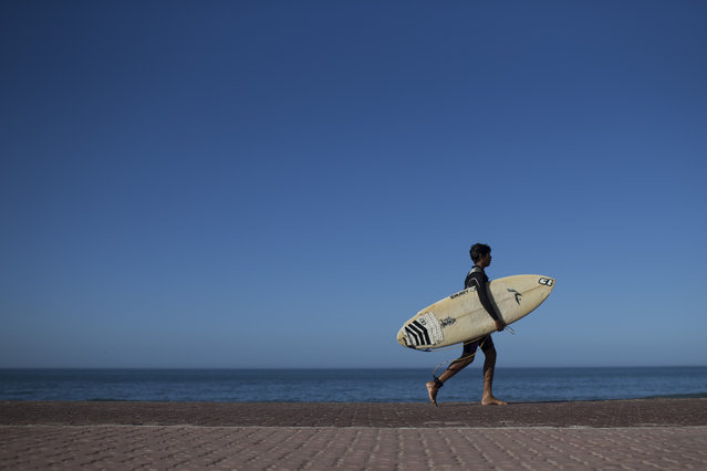 In this  May 21, 2015 photo, Gabriel Santos walks with his board after surfing at Sao Conrado beach in Rio de Janeiro, Brazil. Not long ago, many of these kids were begging on the streets or engaged in crime, but two surf schools serving youth from Rio's largest slum, Rocinha, have helped change that. (Photo by Felipe Dana/AP Photo)