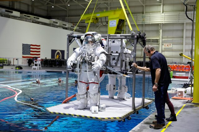 NASA Commercial Crew astronauts Sunita Williams and Josh Cassada are seen lowered into the water at NASA's Neutral Buoyancy Laboratory (NBL) training facility near the Johnson Space Center in Houston, Texas, U.S., July 1, 2019. The exercises included training underwater to simulate space walks, responding to emergencies aboard the space station, and practicing docking maneuvers on a flight simulator. (Photo by Mike Blake/Reuters)