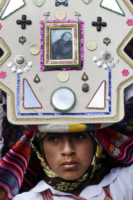 In this June 4, 2015 photo, a Pujili dancer wears a headdress decorated with Catholic and indigenous symbols, as he performs in the streets of Pujili, Ecuador, during the Corpus Christi celebrations, jointly honoring the Holy Communion or Eucharist and Inti the ancient Inca sun god. While most of the region's native peoples identify themselves as Roman Catholic, some practice syncretic rituals that blend the church's traditional beliefs with native customs. (Photo by Dolores Ochoa/AP Photo)