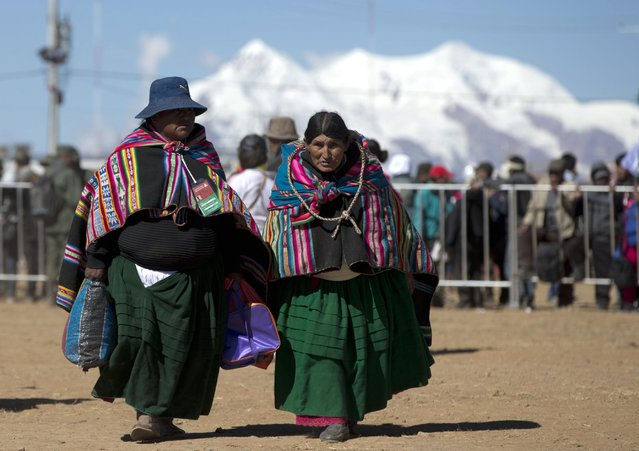 Indigenous women arrive to attend the welcoming ceremony for Pope Francis at the El Alto International airport, 4050 meters (13,615 feet) in El Alto, Bolivia, Wednesday, July 8, 2015.  Due to the altitude, Pope Francis will spend only a few hours in the capital city La Paz, which is near El Alto, during his South American tour. Bolivia is the second of three countries Francis will be visiting on his tour of the continent. (Photo by Eduardo Verdugo/AP Photo)