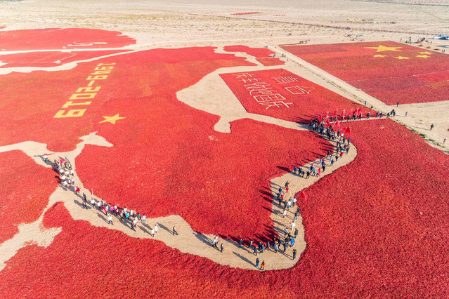 This aerial photo taken on September 23, 2019 shows the image of a Chinese map and a national flag formed by dried chili peppers during the harvest season in Zhangye in China's northwestern Gansu province, as farmers celebrate the 70th anniversary of the founding of the People's Republic of China. (Photo by AFP Photo/China Stringer Network)