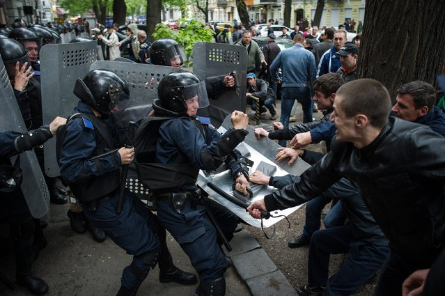 Pro-Russian supporters clash with Ukrainian policemen near the city police department, as participants of a rally attempt to release the pro-Russian supporters arrested during deadly clashes of 02 May, in the South-Ukrainian city of Odessa, Ukraine, 04 May 2014. At least 31 people died in a fire that broke out in a trade union building during clashes 02 May in Odessa, while a Ukrainian military push against separatists in eastern Ukraine stalled after two helicopters were shot down. (Photo by Alexey Furman/EPA)