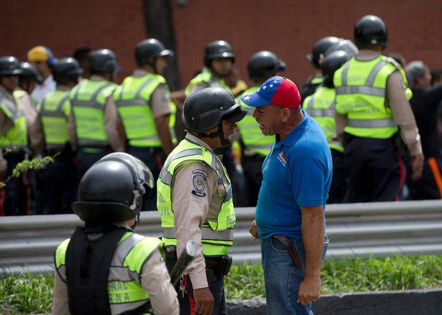 An anti-government demonstrator argues with a Bolivarian National Police officer during a march toward the headquarters of the national electoral body, CNE, in Caracas, Venezuela, Wednesday, May 18, 2016. (Photo by Fernando Llano/AP Photo)