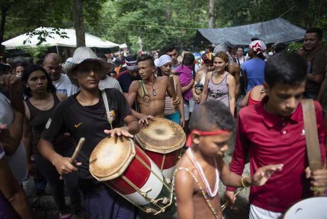 In this photo taken October 12, 2019, people play drums during a procession on Sorte Mountain where followers of indigenous goddess Maria Lionza gather annually in Venezuela's Yaracuy state. The gathering in honor of Maria Lionza is hundreds of years old and draws on Catholicism, Afro-Caribbean religion Santeria and indigenous rituals, all set to a pulse of constant drumming. (Photo by Ariana Cubillos/AP Photo)