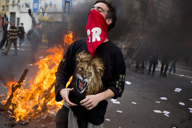 A masked man shout anti-government slogans against government on a street near Congress, where President Michelle Bachelet was presenting the state-of-the-nation report, in Valparaiso, Chile, Saturday, May 21, 2016. An anti-government protest that began as a peaceful march turned rough as some demonstrators threw rocks at police and gasoline bombs at buildings, resulting in the death of one man who reportedly died of asphyxiation. (Photo by Esteban Felix/AP Photo)