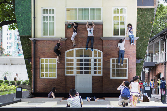 "Visitors pose on Argentine artist Leandro Erlich's optical illusion installation ""Batiment – Oi!"" in Hong Kong May 18, 2014. Erlich creates three-dimensional optical illusions incorporating a huge mirror. (Photo by Tyrone Siu/Reuters)"