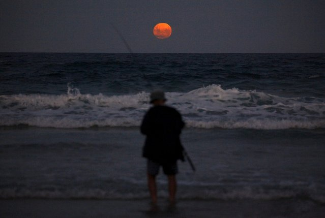 A fisherman prepares to cast his line standing in the surf as a full moon rises at Mollymook Beach, located south of Sydney, Australia, February 23, 2016. (Photo by David Gray/Reuters)
