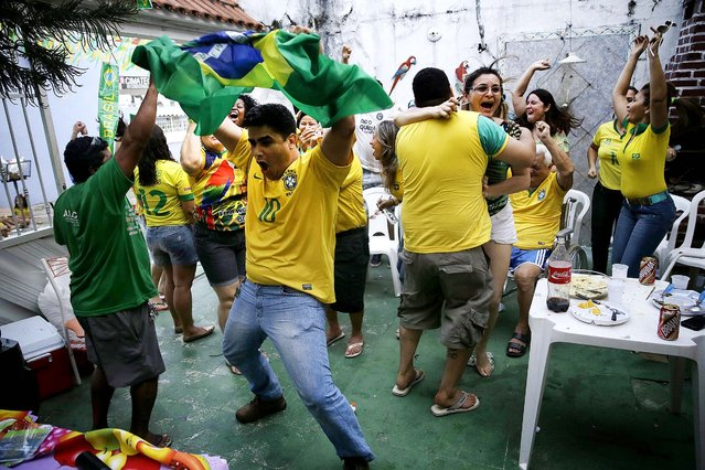 Fans celebrate on the patio of a private residence as they watch a live broadcast of the goal scored by Brazilian midfielder Oscar in the opening match against Croatia, in Manaus, Brazil. (Photo by Martin Mejia/Associated Press)