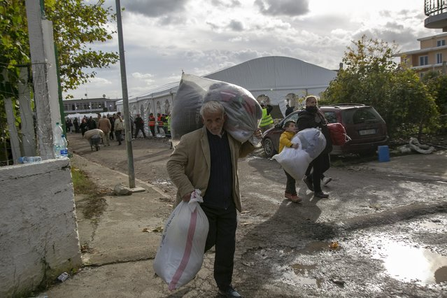 People carry clothes and other supplies distributed by authorities in Thumane, western Albania, Friday, November 29, 2019. The operation to find survivors and recover bodies from Albania's deadly earthquake was winding down Friday as the death toll climbed to 49. (Photo by Visar Kryeziu/AP Photo)