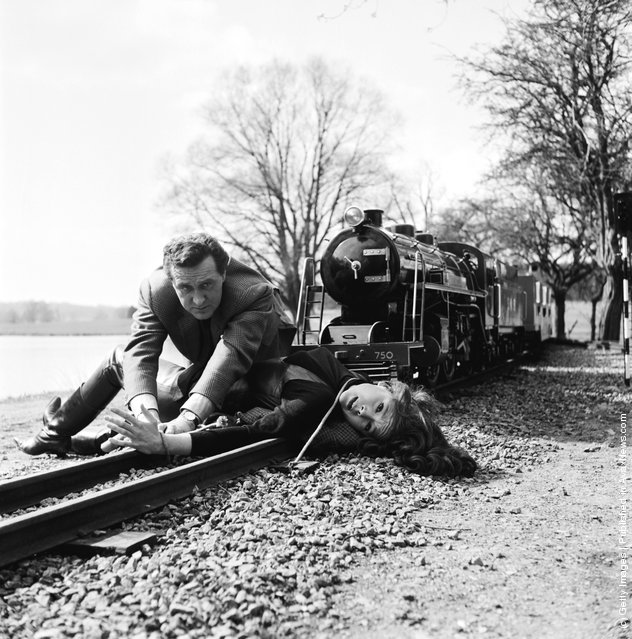 1965: Steed (played by Patrick MacNee) unties Emma Peel (Diana Rigg) as a miniature train comes down the track towards them in an episode of the TV series 'The Avengers'