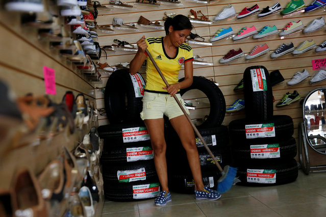 A woman sweeps in front of piles of tires and shoes for sale at a shoe store in Puerto Santander, Colombia, June 3, 2016. (Photo by Carlos Garcia Rawlins/Reuters)