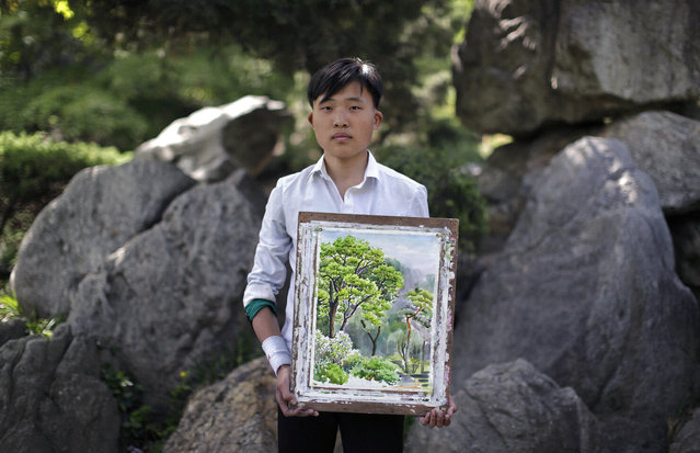 """In this May 10, 2015, photo, Pak Sin Hyok, 16, a student of the Pyongyang University of Fine Art, poses with his unfinished water-color painting of trees in Moranbong or Moran Hill, in Pyongyang, North Korea. Pak has been studying art for three years and hopes to be a professional artist after he graduates in this course that lasts for nine years. His motto: """"To give focus to producing Juche-oriented art and bring glory to the Juche idea, which is the idea of self-reliance"""". (Photo by Wong Maye-E/AP Photo)"""