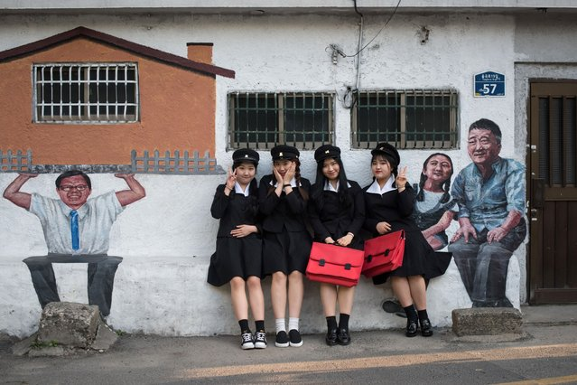 "A group of students pose for a photo wearing 1970's style school uniforms as part of an educational initiative available to visitors to the Naksan ""art village"" in Seoul on April 28, 2017. (Photo by Ed Jones/AFP Photo)"