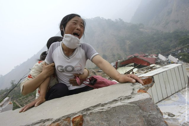 A woman cries as she cannot find her 4-year-old daughter and husband on the top of the ruins of a destroyed school in earthquake-hit Beichuan county, Sichuan province, May 17, 2008