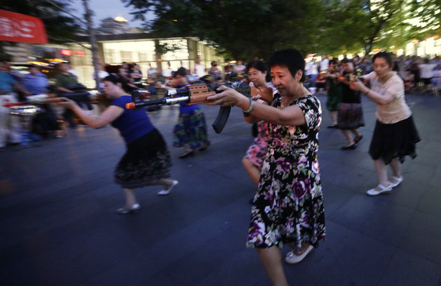 "Local women holding toy guns dance to a revolutionary song as part of their daily exercise at a square outside a shopping mall in Beijing, June 27, 2014. About 30 local residents formed this ""Nanguan"" art group that enjoys performing and dancing to revolutionary songs as part of their nightly fitness activity. (Photo by Jason Lee/Reuters)"