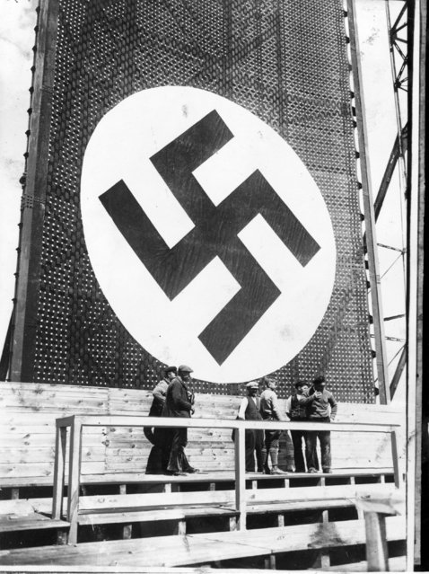 30th April 1934:  One of the huge swastika signs being hung during preparations for a May Day rally where Hitler will address a crowd of nearly 2,000,000 in the Tempelhof Field in Berlin
