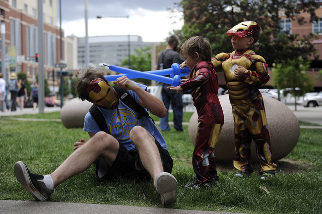 Dewey Pruitt gets attacked with balloon swords by his sons Corben, 5, and Ronin, 4, as they play outside during Denver Comic Con at the Colorado Convention Center in Denver, Colorado on June 14, 2014. (Photo by Seth McConnell/The Denver Post)