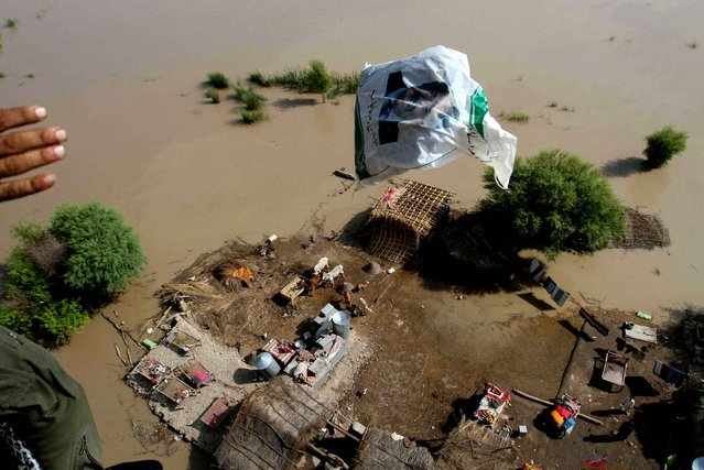 Pakistan army helicopter drops a bag of relief to villagers stranded in floodwater in Rajanpur, Pakistan, Thursday, August 6, 2015. Torrential rains and flash floods have hit various villages and cities across the country, forcing the authorities to declare an emergency and issue alerts. (Photo by Asim Tanveer/AP Photo)