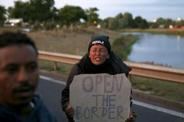 """An migrant cries as she shouts slogans next to the French police during a protest on the motorway in Calais, France, August 7, 2015. For most of the 3,000 inhabitants of the """"Jungle"""", a shanty town on the sand dunes of France's north coast, the climax of each day is the nightly bid to sneak into the undersea tunnel they hope will lead to new life in Britain. (Photo by Juan Medina/Reuters)"""