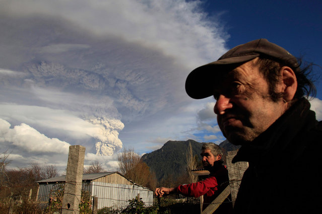 Locals stay in front of their home as ash and steam rise from the Puyehue-Cordon Caulle volcanic chain near Osorno city in south-central Chile June 5, 2011
