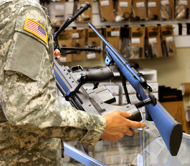 "A member of the Utah National Guard examines a gun at the ""Ready Gunner"" gun store in Provo, Utah, U.S., June 21, 2016. (Photo by George Frey/Reuters)"