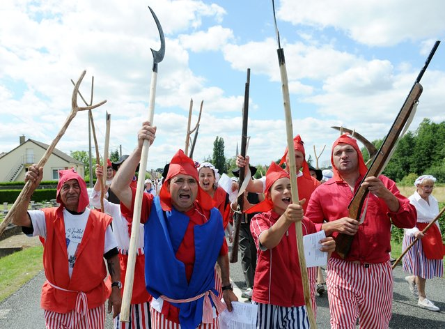 Villagers in revolutionary costumes gesture and take part in the commemorating of the storming of the Bastille during Bastille Day, in Lavaré, western France. In the dark night the villagers will take the Bastille and will set it on fire while dancing the carmagnole. (Photo by Jean-Francois Monier/AFP Photo)