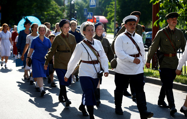Military enthusiasts dressed as Red Army soldiers and civilians from the World War Two period march as they mark the 75th anniversary of the Nazi Germany invasion, in Brest, Belarus June 21, 2016. (Photo by Vasily Fedosenko/Reuters)