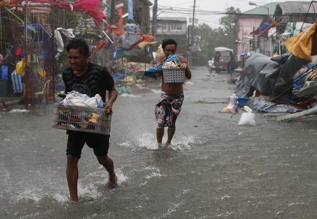 Residents carry their belongings as Typhoon Rammasun (locally named Glenda) hit the town of Imus, Cavite southwest of Manila, July 16, 2014.  (Photo by Erik De Castro/Reuters)
