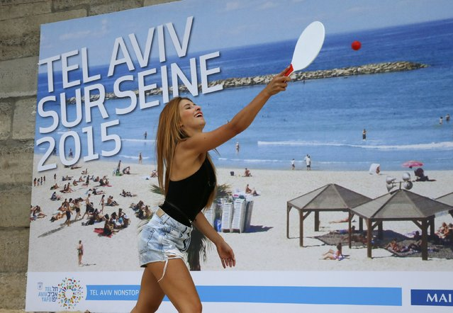 """A woman plays paddle ball on a artificial sand beach at """"Paris Plages"""" near a giant photo promoting the """"Tel Aviv on Seine"""" event, in Paris, France, August 13, 2015. (Photo by Pascal Rossignol/Reuters)"""