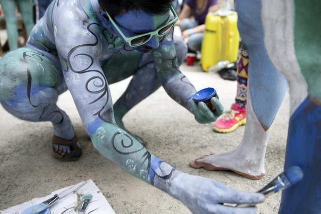 Models help paint one another at Columbus Circle as body-painting artists gathered to decorate nude models as part of an event featuring artist Andy Golub, Saturday, July 26, 2014, in New York. Golub says New York was the only city in the country that would allow his inaugural Bodypainting Day. (Photo by John Minchillo/AP Photo)