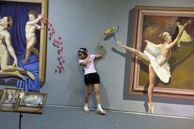 A visitor to an exhibit of art works that give the illusion of being three dimensional poses near the depiction of a ballet dancer in Beijing Saturday, July 26, 2014. (Photo by Ng Han Guan/AP Photo)