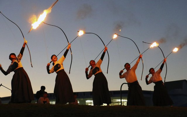 High school students fire flaming arrows, marking the start of an annual fire festival at a cape facing the Pacific Ocean in Kushimoto, Wakayama Prefecture, western Japan, on February 1, 2020. (Photo by Kyodo News via Getty Images)