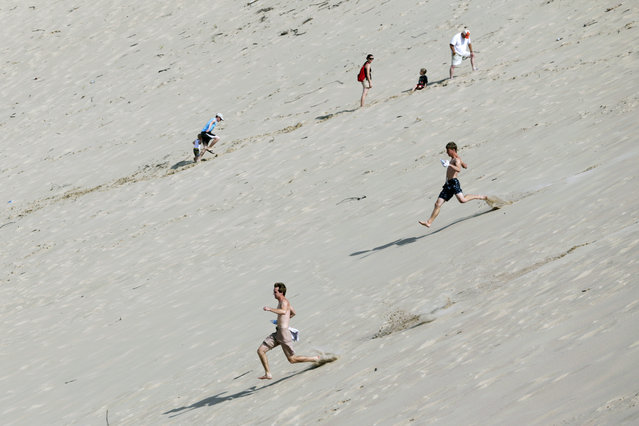 Alec Troemel, 19, bottom, and Andrew Westgate, 19, both of  Mundelein, Ill., race down a dune as a family treks up the steep hill during an outing at Warren Dunes State Park, Wednesday, August 6, 2014, in Bridgman, Mich. (Photo by Julio Cortez/AP Photo)