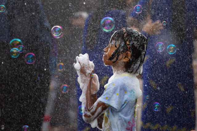 A girl plays with soap suds during celebrations for the Thingyan festival, also known as the Buddhist New Year, in Yangon on April 13, 2019. (Photo by Sai Aung Main/AFP Photo)