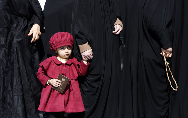 A young Iranian girl holds her mother's hand as they wait in line at a polling station set up at the Abdol Azim shrine during the parliamentary elections in Shahr-e-Ray, Tehran Province, Iran, 21 February 2020. Iranians are heading to the polls to elect their representatives to the Islamic Consultative Assembly amid a worsening economic crisis and escalating tensions with the US. (Photo by Abedin Taherkenareh/EPA/EFE)