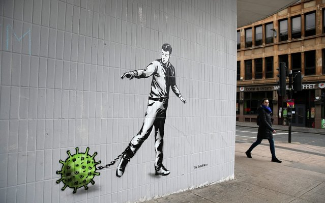 A person walks past a piece of art by the artist, known as the Rebel Bear after it appeared on a wall on Bath Street in Glasgow on April 3, 2020. The new addition to Glasgow's street art is capturing the global Coronavirus crisis. The piece features a man pulling a chain with a germ attached to it as the UK continues in lockdown to help curb the spread of the coronavirus. (Photo by Andrew Milligan/PA Images via Getty Images)