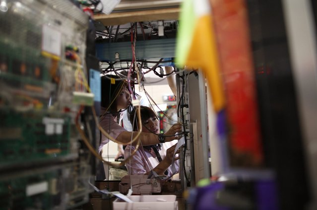 Dynam employees are seen during the installation of pachinko machines, ahead of the opening of the hall in Fukaya, north of Tokyo July 16, 2014. (Photo by Issei Kato/Reuters)