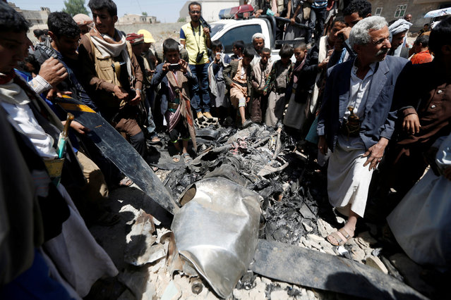 People gather around the engine of a drone aircraft which the Houthi rebels said they have downed in Sanaa, Yemen October 1, 2017. (Photo by Khaled Abdullah/Reuters)